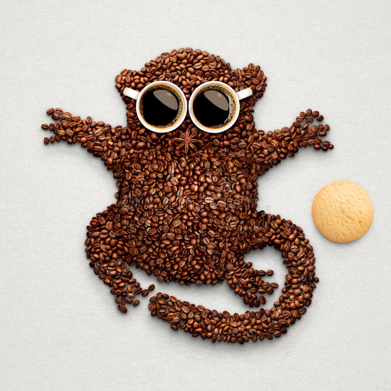 Tarsier with cookie. A funny tarsier made of roasted coffee beans, two cups and star anise with an oatmeal cookie stock photography