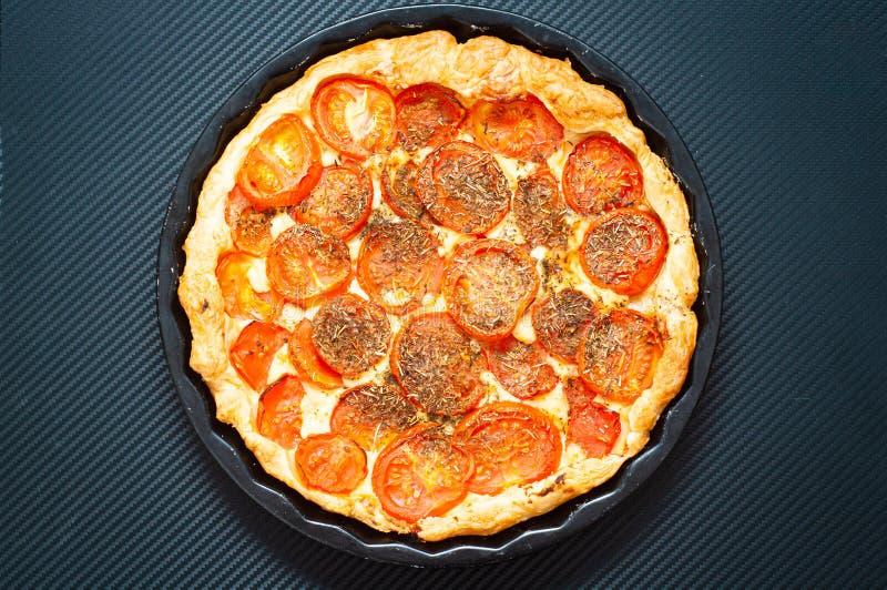 Tart di pomodoro e di senapa francesi, cotte in pasta di puff e condite con erbe aromatiche di provenienza fotografia stock