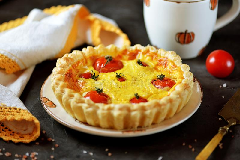 Tart pie with cheese, eggs, cream and cherry tomatoes on puff pastry. royalty free stock photos