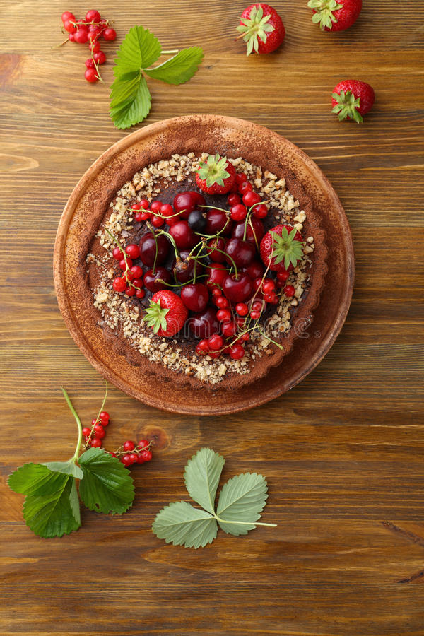 Tart with summer fruits on wood. Food top view royalty free stock images