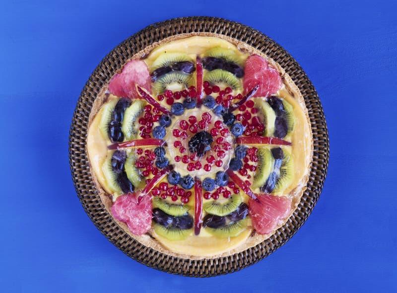 Tarta de la fruta con crema y bayas en soporte de la torta, las flores y la toalla imágenes de archivo libres de regalías