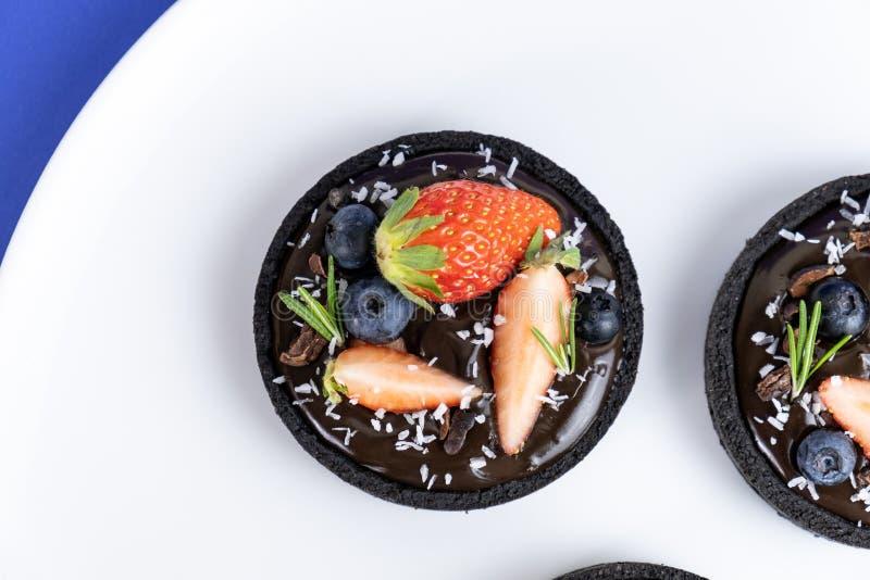 Tarta del chocolate de la corteza de la galleta con el sistema del ar?ndano y de la fresa en fondo azul fotografía de archivo libre de regalías