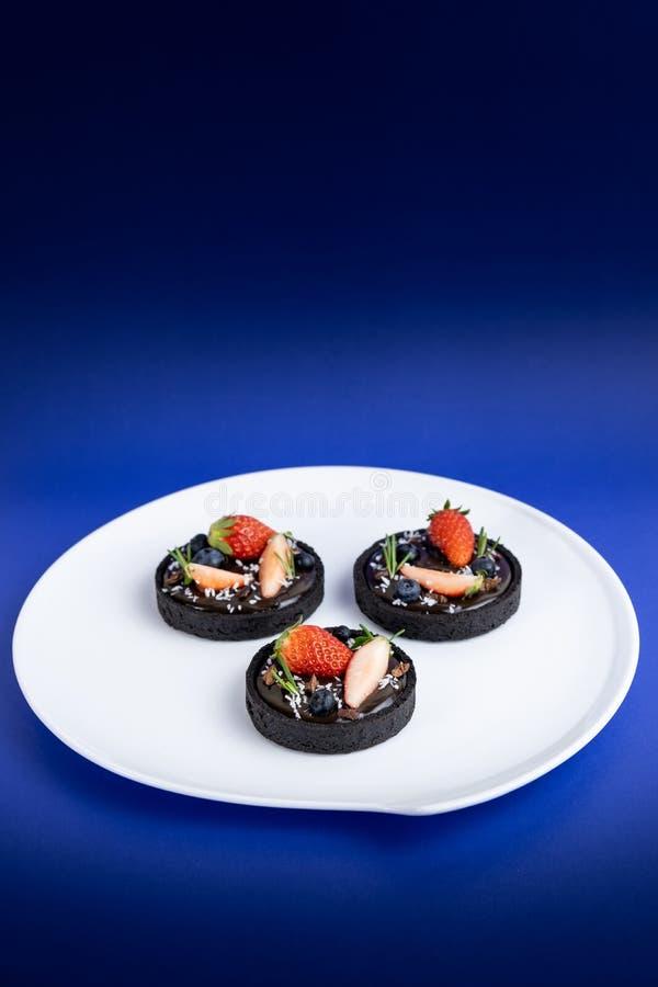 Tarta del chocolate de la corteza de la galleta con el sistema del ar?ndano y de la fresa en fondo azul fotos de archivo libres de regalías