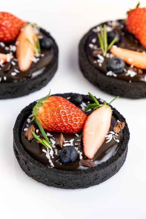 Tarta del chocolate de la corteza de la galleta con el sistema del ar?ndano y de la fresa en fondo azul imagenes de archivo