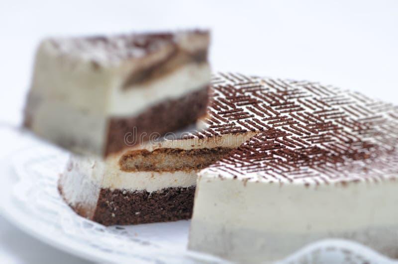 Tarta del Tiramisu en la cuchara del metal, polvo de cacao en la torta, torta de cumpleaños en la placa blanca, pastelería, fotog imagenes de archivo