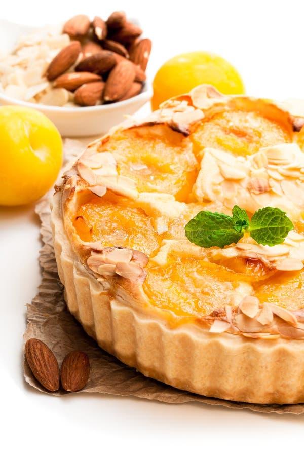 Tarta deliciosa con el ciruelo amarillo y las almendras aislados en blanco fotos de archivo