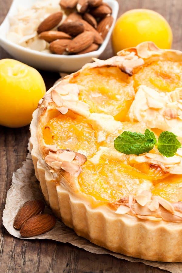 Tarta deliciosa con el ciruelo y las almendras amarillos en la tabla de madera foto de archivo libre de regalías