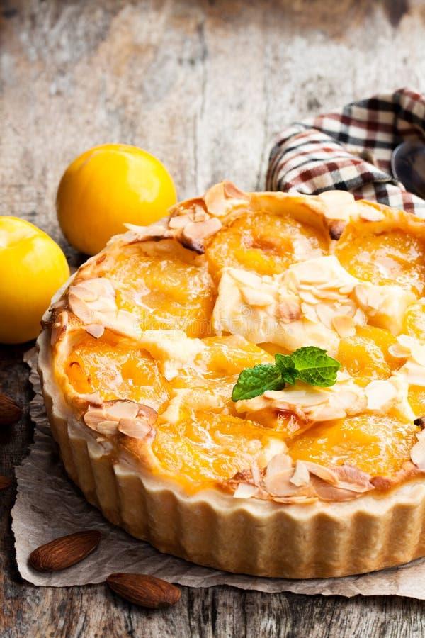 Tarta deliciosa con el ciruelo y las almendras amarillos en la tabla de madera foto de archivo