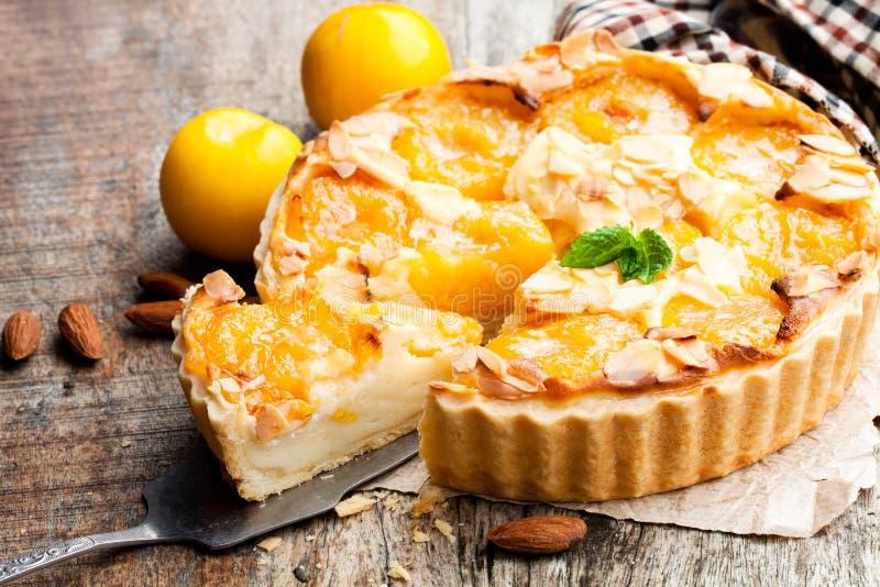 Tarta deliciosa con el ciruelo y las almendras amarillos en la tabla de madera fotografía de archivo libre de regalías