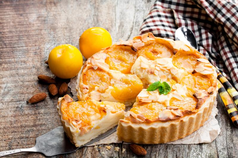 Tarta deliciosa con el ciruelo y las almendras amarillos en la tabla de madera imagen de archivo libre de regalías