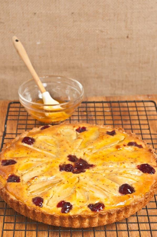 Tarta hecha en casa, recientemente cocida del arándano de la pera con las almendras que se refrescan en un estante de enfriamient fotografía de archivo libre de regalías