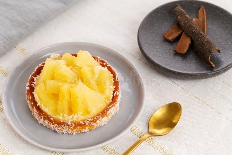 Tarta o tarta de piña con coco en cuchara dorada y un plato pequeño con bastones de canela en un paño blanco y dorado de mesa imagen de archivo