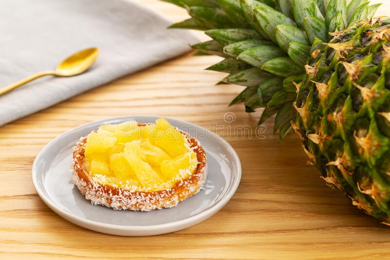 Tarta o tarta de piña con coco rallado a base de una fruta entera de piña, servilleta gris y cuchara dorada, fondo de madera foto de archivo libre de regalías