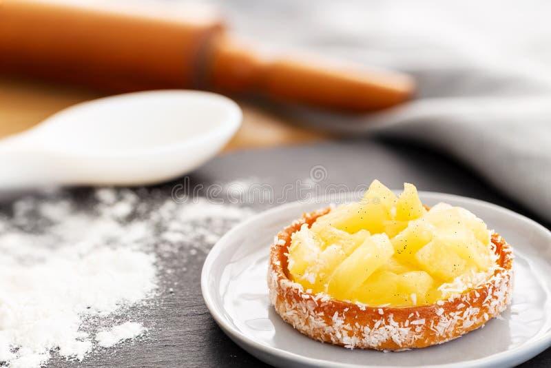 Tarta o tarta de piña con coco rallado en una pequeña placa sobre una pizarra con harina y utensilios de horneado fotografía de archivo libre de regalías