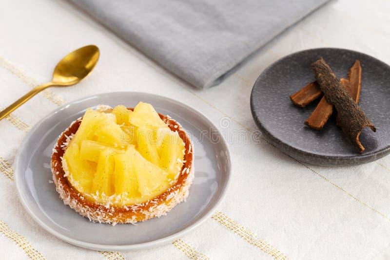 Tarta o tarta de piña con coco rallado por una cuchara dorada y un plato pequeño con bastones de canela sobre un paño blanco de m imagen de archivo libre de regalías