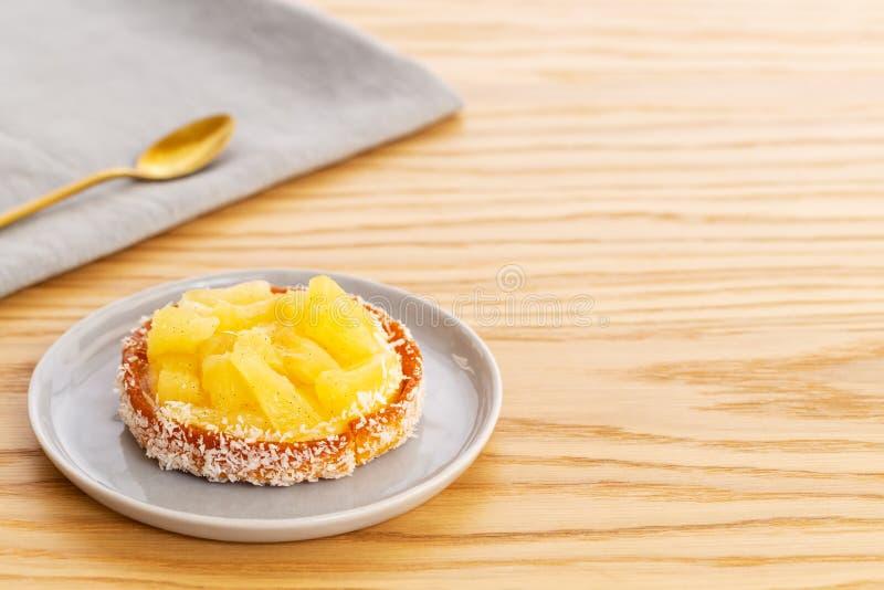 Tarta o tarta de piña con coco rallado sobre una servilleta gris con una cuchara dorada sobre un fondo de madera con una copia imagen de archivo libre de regalías
