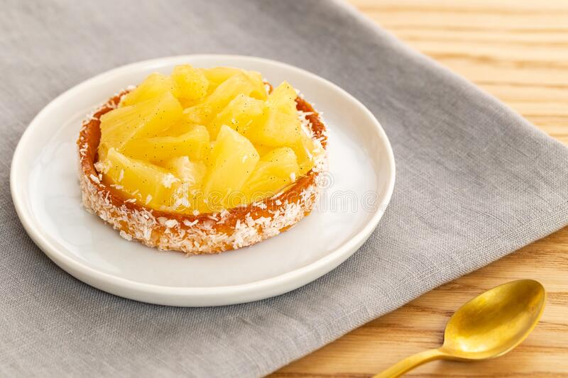 Tarta o tarta de piña con coco rallado sobre una servilleta gris con una cuchara dorada sobre un fondo de madera imagen de archivo