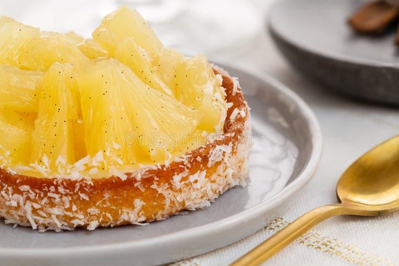 Tarta o tarta de piña con coco rallado y una cuchara dorada sobre un paño blanco y dorado imágenes de archivo libres de regalías