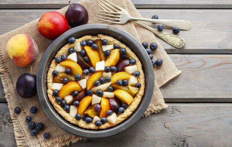 Tarta z brzoskwinią, banią, śliwką, bonkretą i czarną jagodą w jesień secie, fotografia royalty free