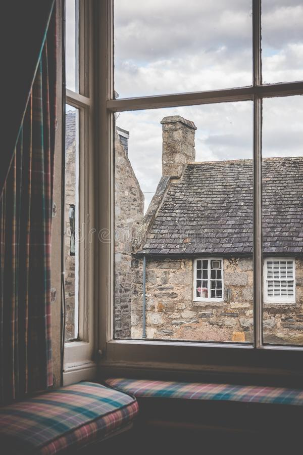 Tartan curtains and cushions on a window seat in an old country. Scottish village. shot from indoors looking out towards these old georgian buildings stock image