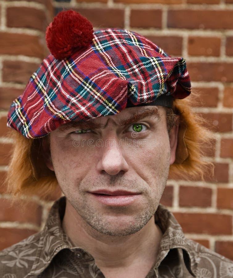 Tartan madness (. Man in joke tartan beret and red wig with tartan texture in his eyes royalty free stock image