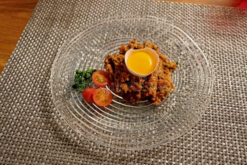 Tartare стейка говядины с яичным желтком на стеклянной пластинке стоковые фотографии rf