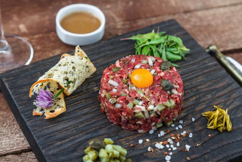 Tartare стейка, который служат с сырцовым яичным желтком триперсток и другим tartare ингридиентом Мясное блюдо стоковые фотографии rf
