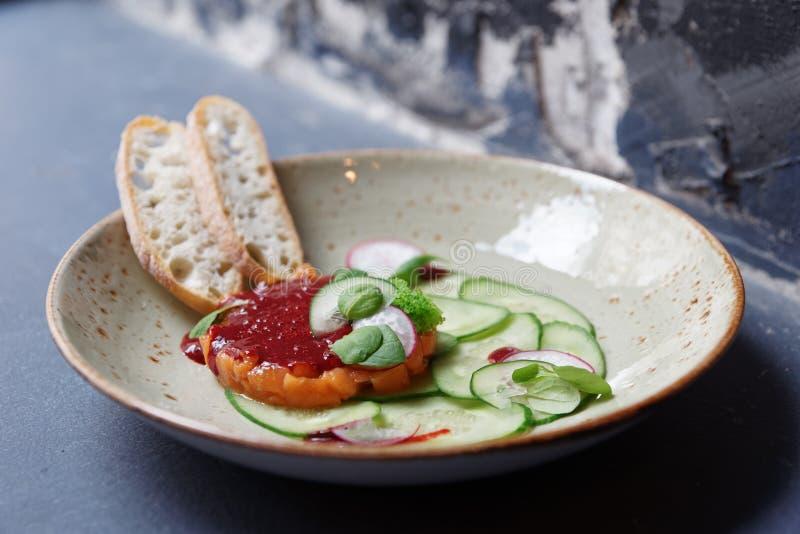 Tartare de color salmón con los pepinos y la salsa roja foto de archivo