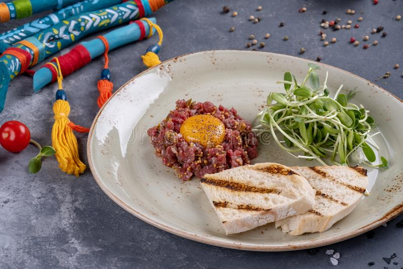 Tartare delicioso com p?o e salada brindados em uma placa Refei??o saud?vel do almo?o feita da carne crua Culin?ria francesa cl?s foto de stock