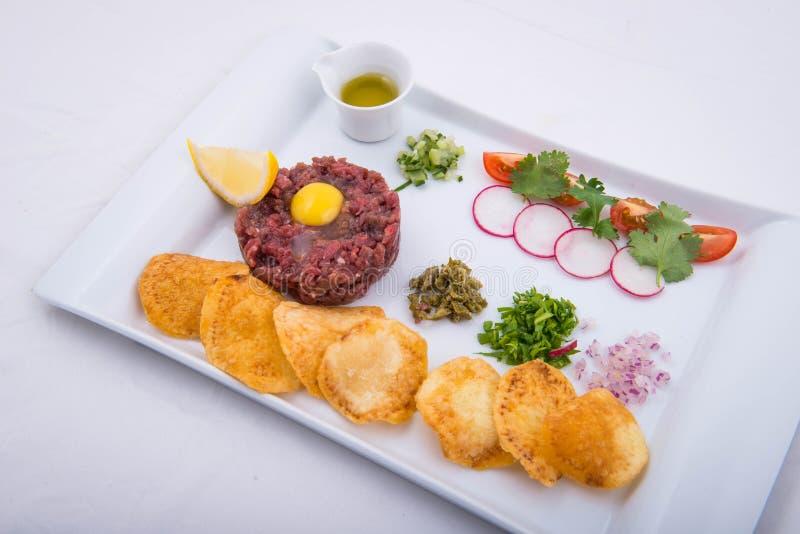 Tartaro del manzo con le patatine fritte e l'olio d'oliva fotografia stock