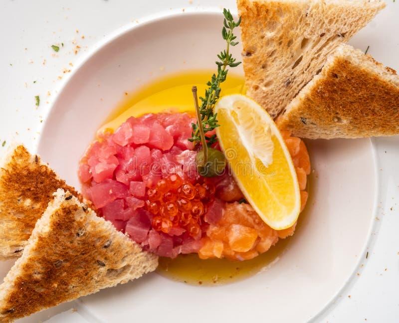 Tartaro del salmone e del tonno con i capperi, il limone ed il caviale rosso immagini stock