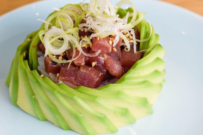 Tartaro della carne del tonno rosso su un letto di riso, guarnito con le fette di avocado e le fette sottili di porri, sesamo in  fotografia stock