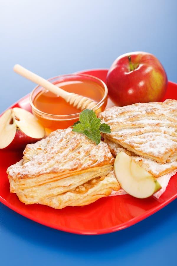 Tartas de manzanas en pedazos de la placa, de la miel y de la manzana alrededor fotografía de archivo