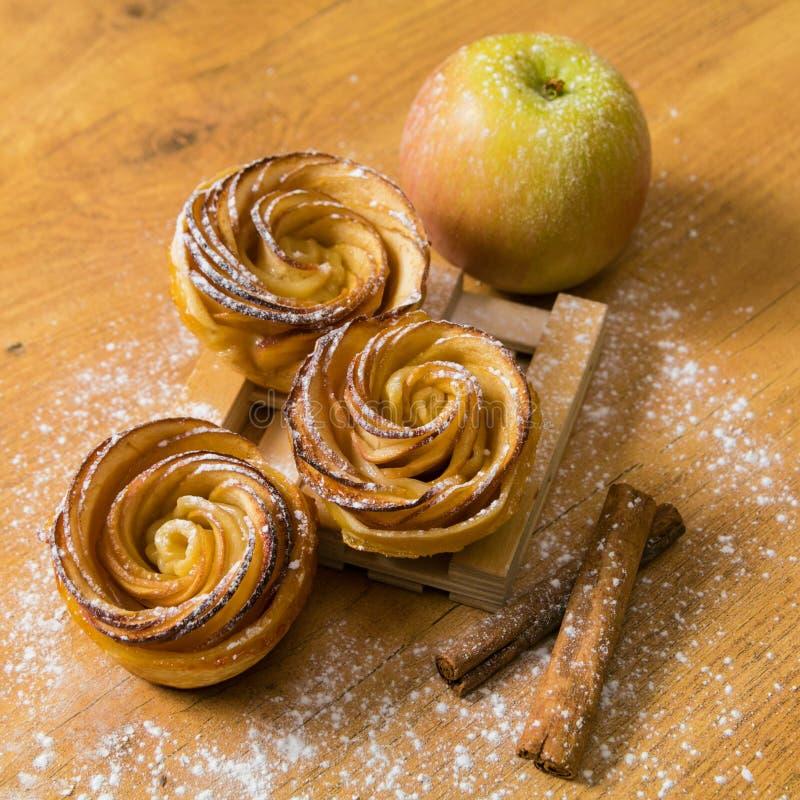 Tartas de manzanas hechas en casa con el azúcar del canela y de formación de hielo en fondo de madera Mini tartas de Apple Rose imagenes de archivo