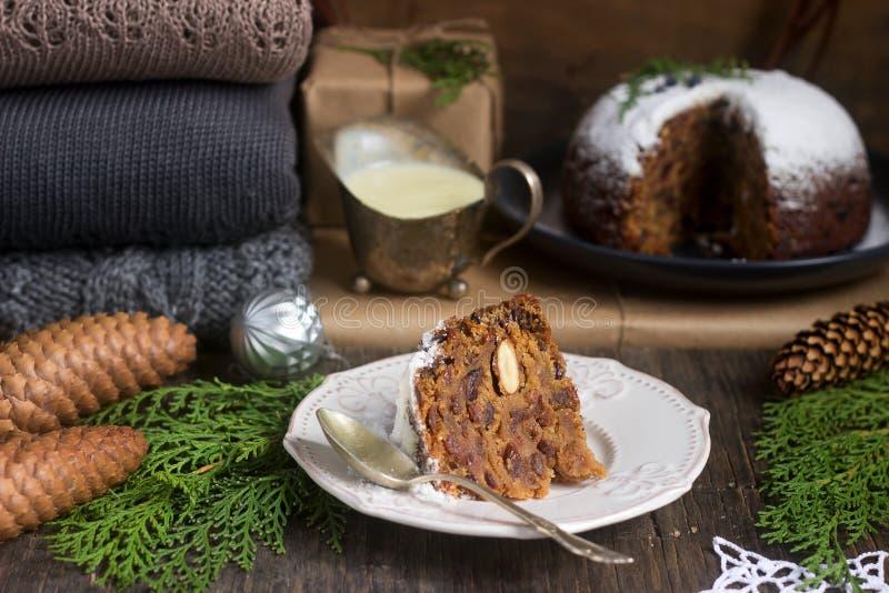 Tarte anglais de Noël avec de la sauce à vanille dans la décoration de fête Type rustique images stock