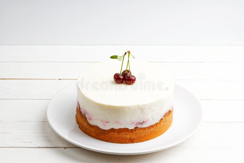 Tarte aux cerises faite maison avec du yaourt sensible remplissant sur la table en bois blanche photo stock