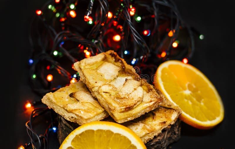 Tarte aux pommes avec des oranges et des lumières de Noël images libres de droits