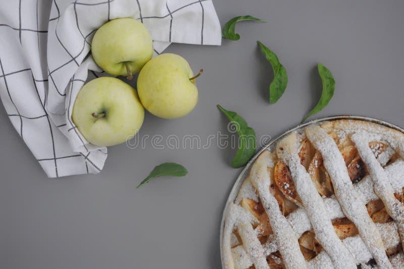 Tarte aux pommes avec la serviette blanche sur le fond gris Dessert Gâteau fait maison avec le thé noir et le tamis Automne flatl photographie stock libre de droits