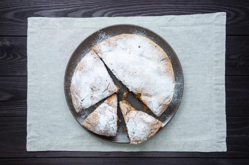 Tarte aux pommes coupée en tranches dans le plat sur le fond en bois foncé photo libre de droits