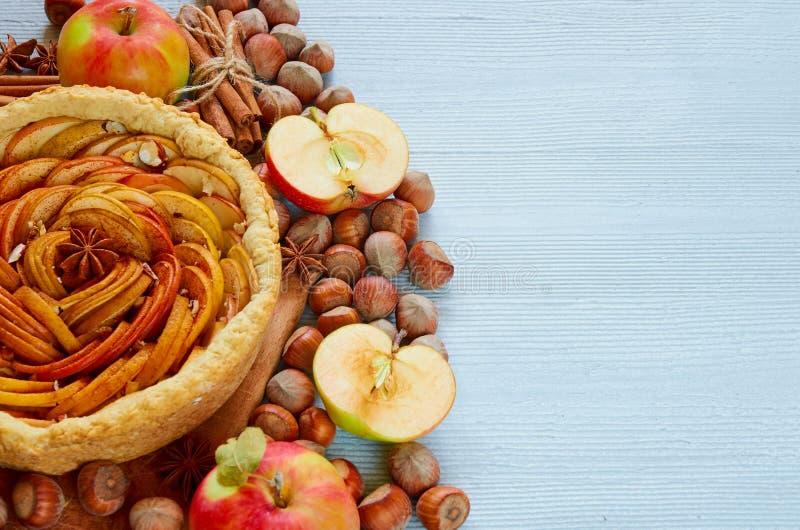 Tarte aux pommes d'automne décorée de divers ingrédients - pommes coupées en tranches fraîches, noisettes, épices - anis, cannell photo stock