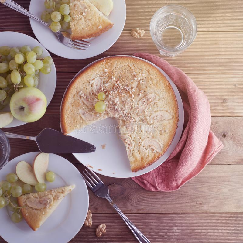 Tarte aux pommes fraîchement cuite au four rustique, fond en bois foncé Fruits d'automne : raisins, pommes, écrous Dessert toujou photos stock
