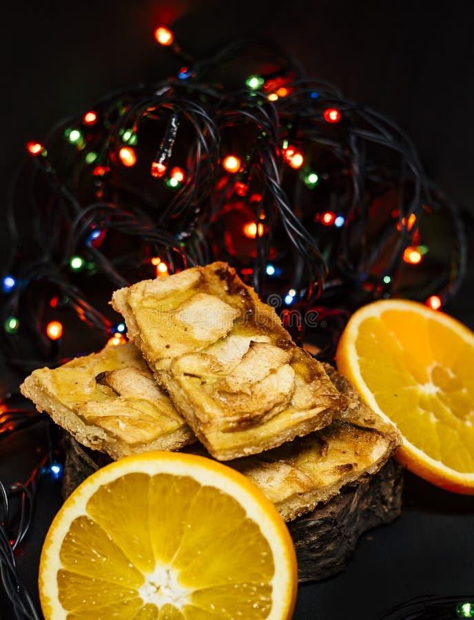 Tarte aux pommes savoureuse avec des oranges et des lumières de Noël images libres de droits