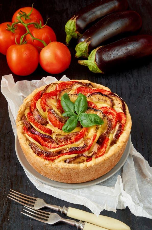 Tarte avec des aubergines, des tomates et le fromage du plat gris décoré des feuilles de basilic et des fourchettes fraîches de v photographie stock