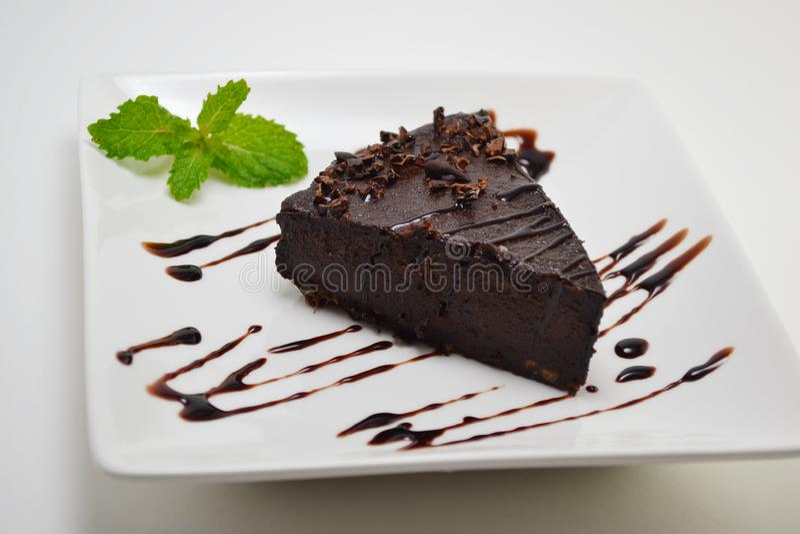 Tarte cru de Vegan de chocolat servi du plat blanc photographie stock