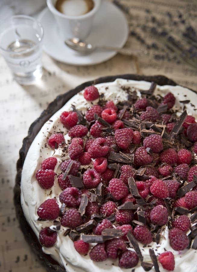 Tarte délicieuse de chocolat avec de la crème et la framboise sur le fond des notes de cru, avec une tasse d'expresso aromatisé photos libres de droits