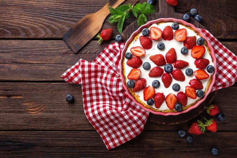Tarte délicieux de fraise avec la myrtille fraîche et la crème fouettée sur la table rustique en bois, gâteau au fromage photo libre de droits