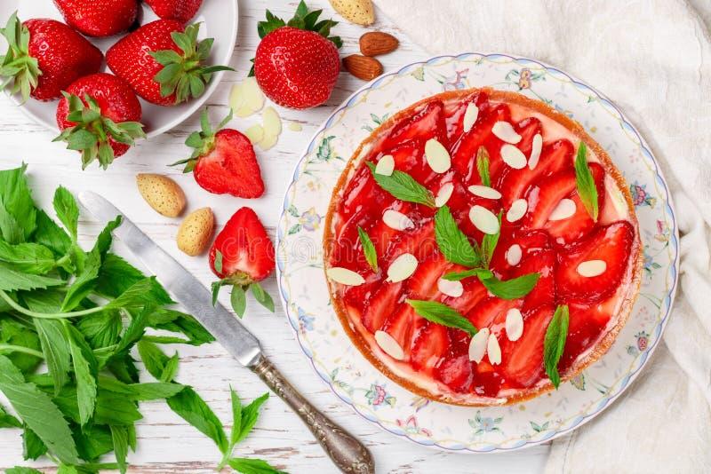 Tarte d?licieuse faite maison de fraise avec la cr?me anglaise ou la cr?me fouett?e, avec les feuilles en bon ?tat et les p?tales image stock
