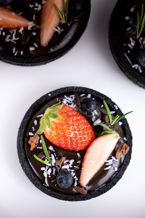 Tarte de chocolat de cro?te de biscuit avec l'ensemble de myrtille et de fraise sur le fond bleu photos stock