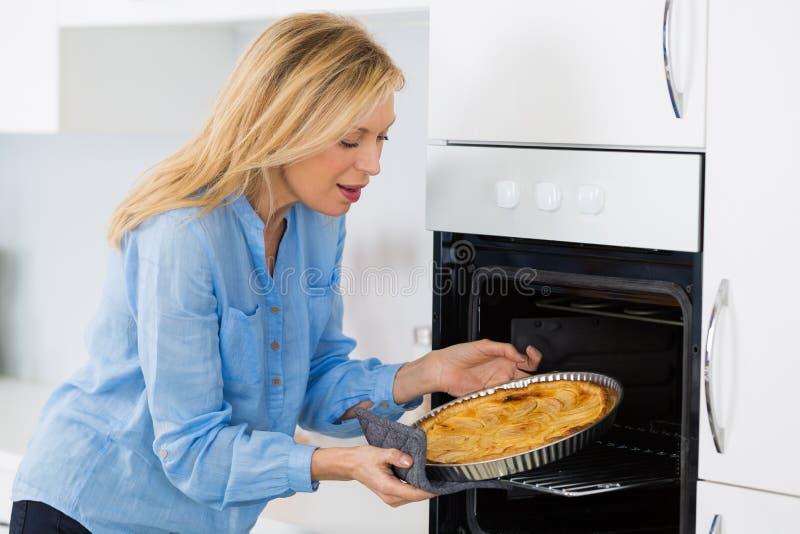 Tarte de cuisson de femme blonde mûre en four images libres de droits