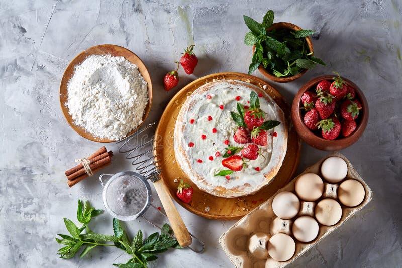 Tarte de fraise couverte de crème sure fouettée entourée par les ingrédients organiques au-dessus du fond blanc, configuration d' photographie stock